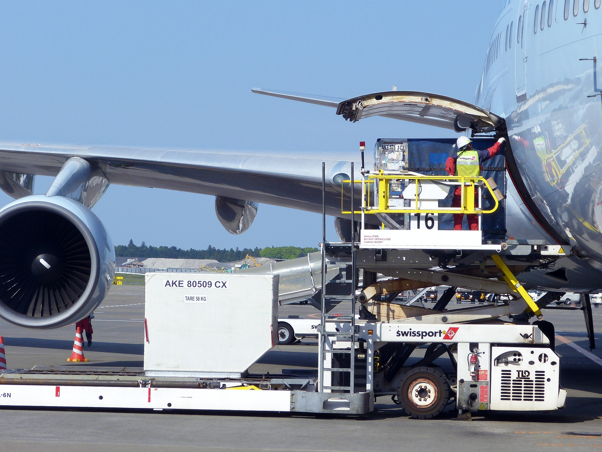 a ULD containing air freight behind loaded on the lower deck of an airplane